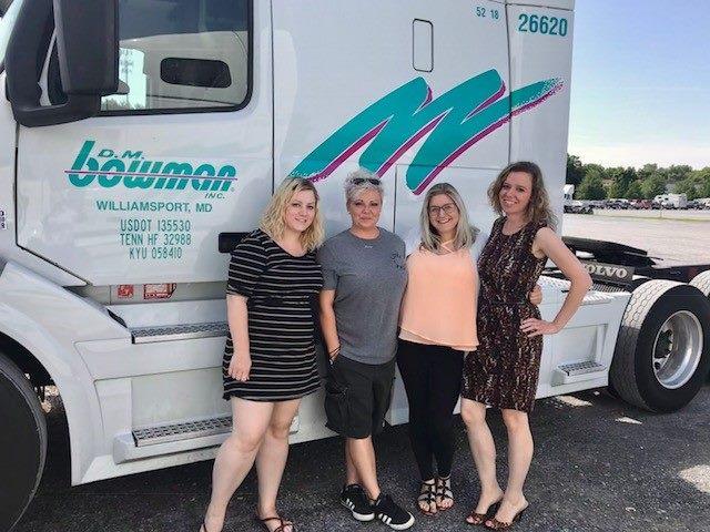 4 women standing in front of Bowman truck